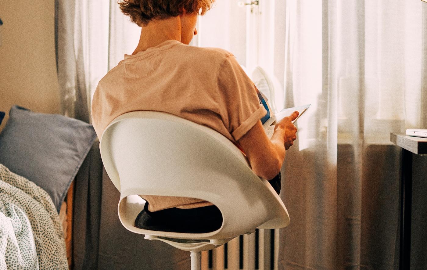 Um estudante sentado numa cadeira giratória virado para a janela com os pés apoiados no radiador à sua frente.