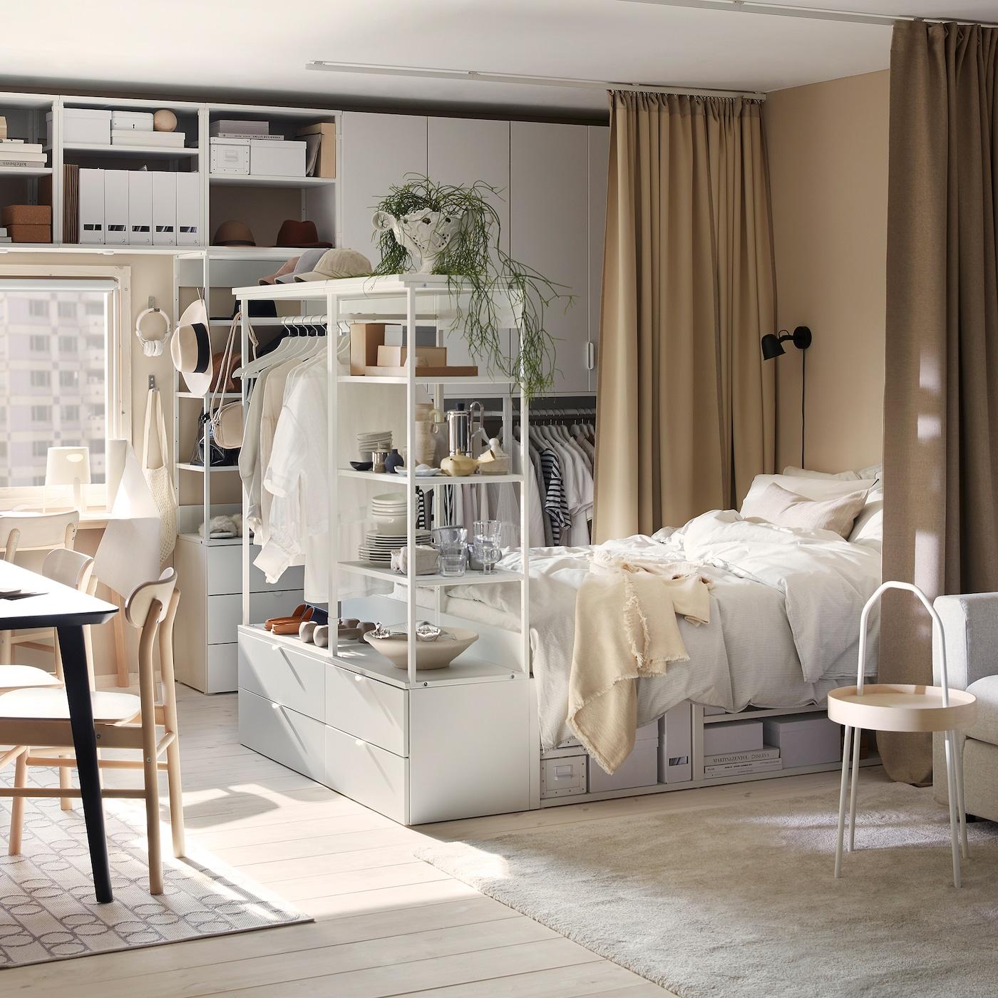Um estúdio com combinações de arrumação PLATSA e estrutura de cama em branco, uma mesa de refeição em preto e cortinados em bege.