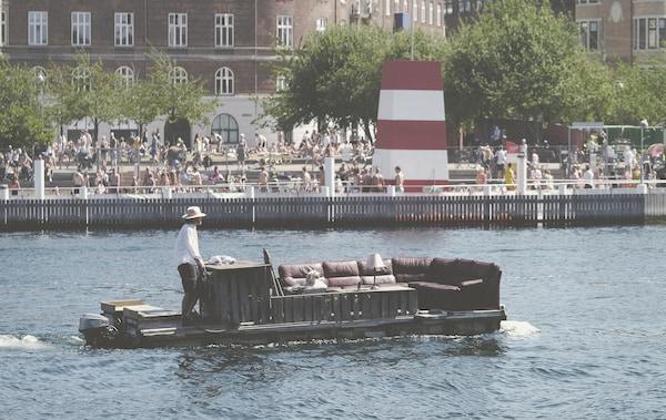 Um homem a conduzir um sofá grande sobre um barco no rio, com multidões, edifícios e árvores na margem.