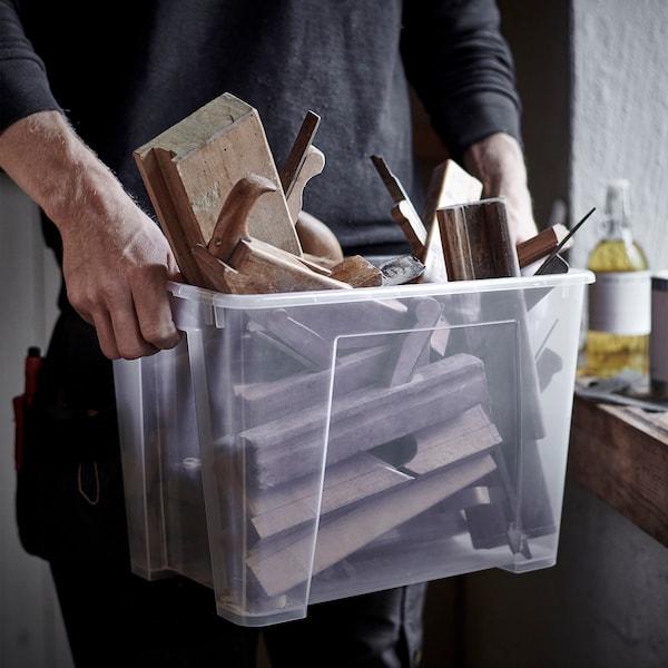 Um homem a transportar uma caixa de plástico SORTERA transparente cheia de pedaços de madeira e ferramentas.