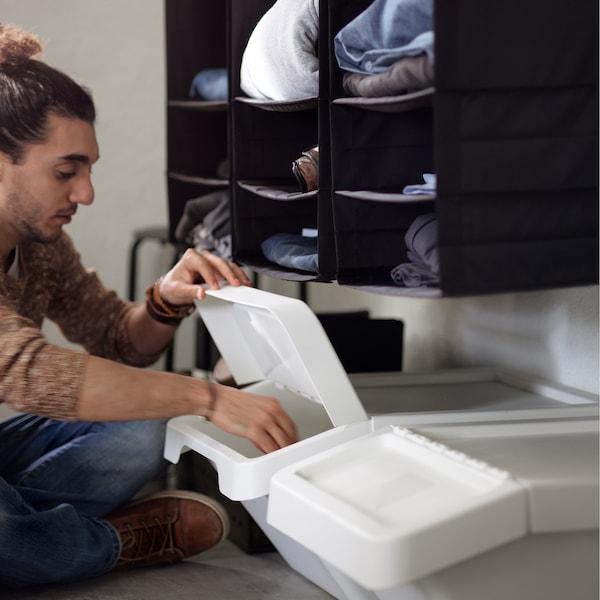 Um homem sentado no chão, a levantar a tampa de um caixote de plástico SORTERA branco, igualmente no chão.