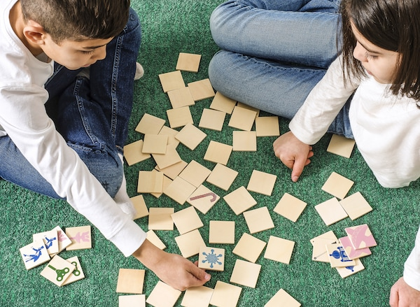 Um menino e uma menina sentados num tapete verde a jogar um jogo.
