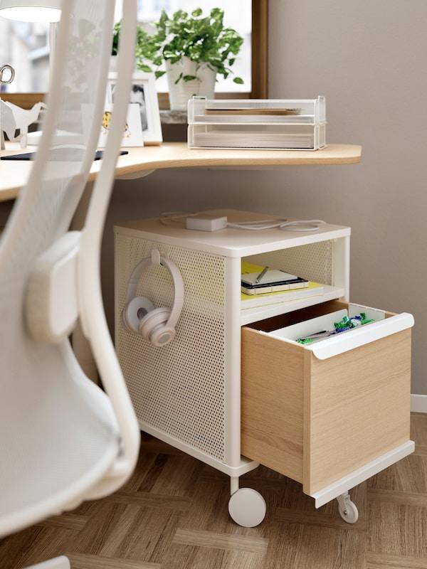 Um módulo de arrumação BEKANT debaixo de uma secretária com uma gaveta aberta e objetos na prateleira. Auscultadores pendurados num gancho lateral.