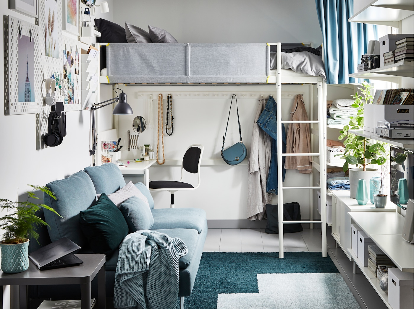 Um pequeno estúdio em tons de cinzento, verde e branco, com uma cama alta e secretária por baixo.