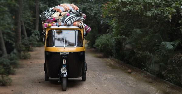 Um pequeno táxi, em preto e amarelo, na Índia, a carregar almofadas coloridas às riscas na parte superior.