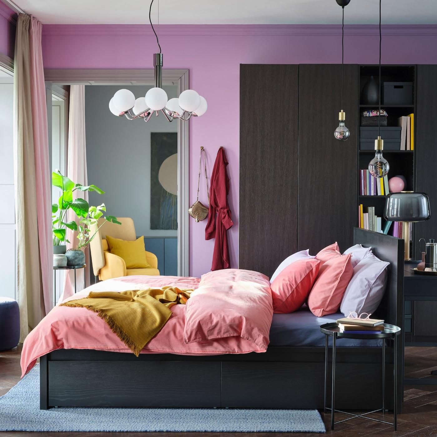 Um quarto colorido com paredes em lilás, roupa de cama em castanho claro-vermelho, uma manta em amarelo e um roupeiro e estrutura de cama em preto-castanho.
