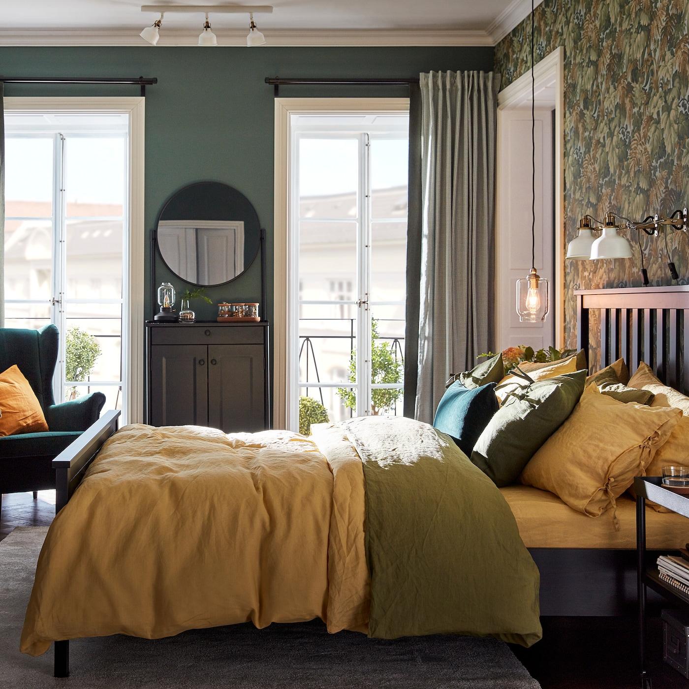 Um quarto com uma cama com almofadas e capas de edredão em verde e amarelo, um armário com um espelho e uma poltrona em verde.