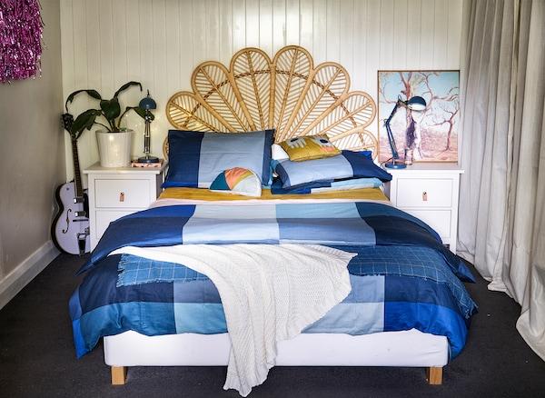 Um quarto com uma cama com cabeceira em verga, roupa de cama em azul e mesas de cabeceira em branco.