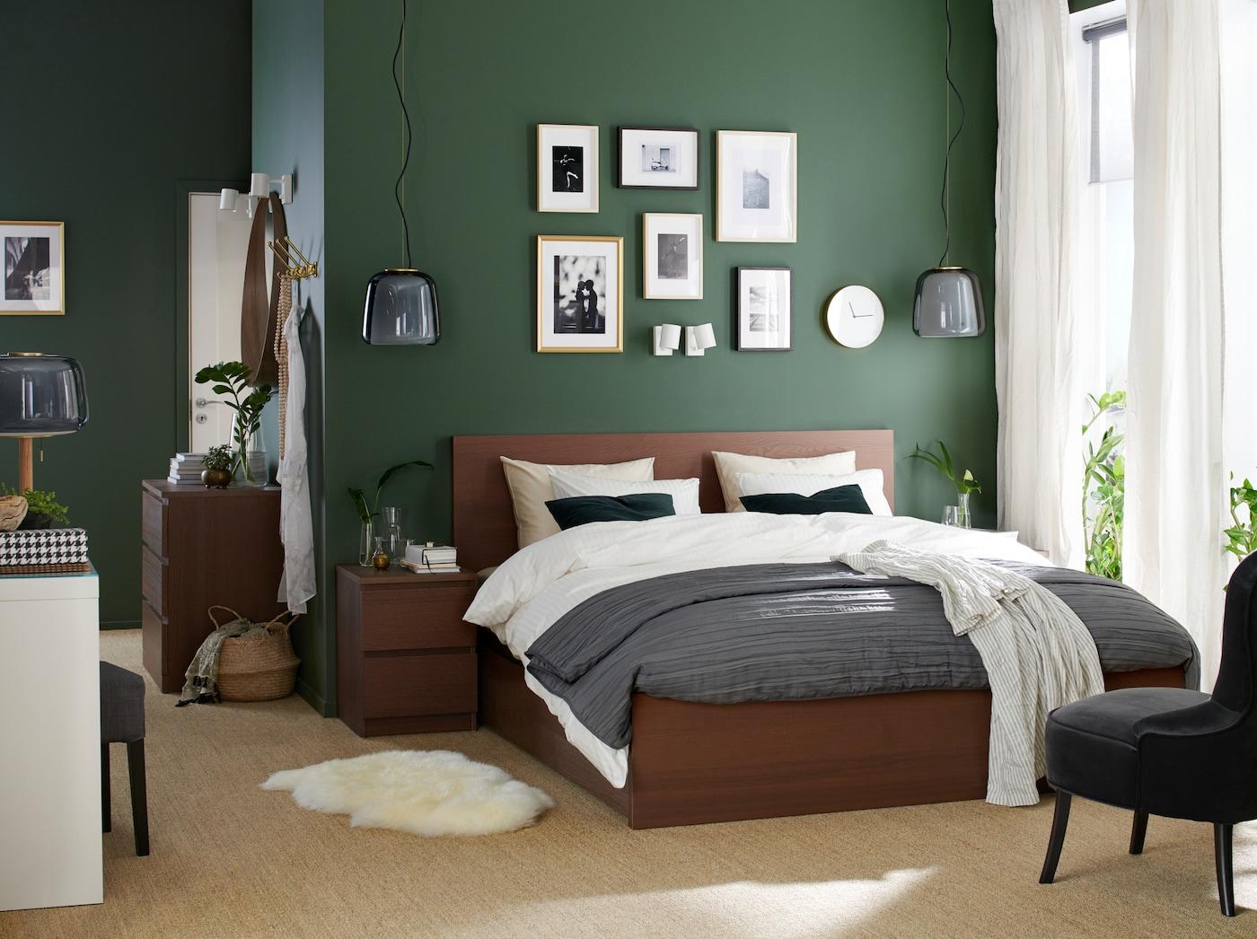Um quarto com uma estrutura de cama e mesa de cabeceira em chapa de freixo com velatura castanha, um toucador branco e uma poltrona em cinzento.