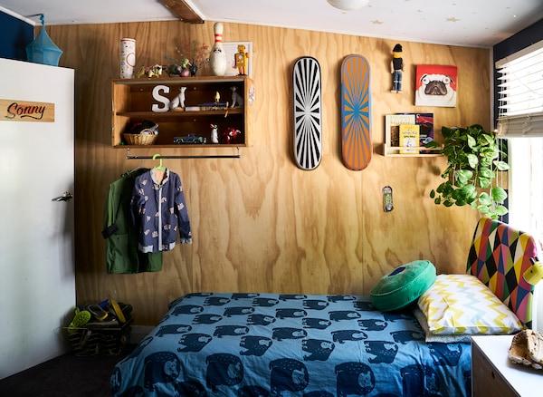 Um quarto de criança com prateleiras, pranchas de skate numa parede de madeira e roupa de cama com padrão em azul.