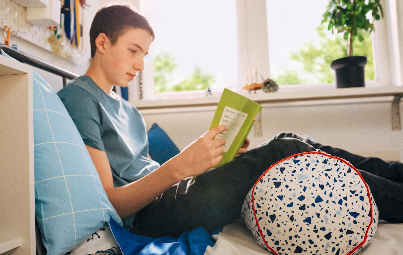 Um rapaz em idade escolar está sentado na cama a ler, encostado a uma almofada e com as pernas sobre uma almofada MÖJLIGHET.