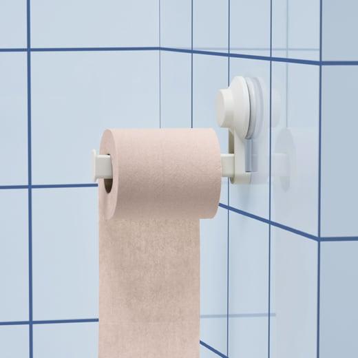 Um rolo rosa pendurado no porta-rolos com ventosa numa parede de azulejo azul.