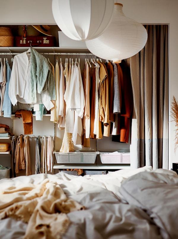 """Um roupeiro com cortinados como """"portas"""" e uma combinação de cabides e prateleiras para malas de viagem e caixas para os artigos mais pequenos."""