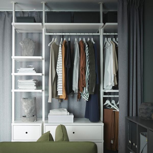 Um sistema de arrumação ELVARLI em branco com roupas, revistas e peças decorativas arrumadas. Em frente está um cortinado cinzento que o pode tapar.