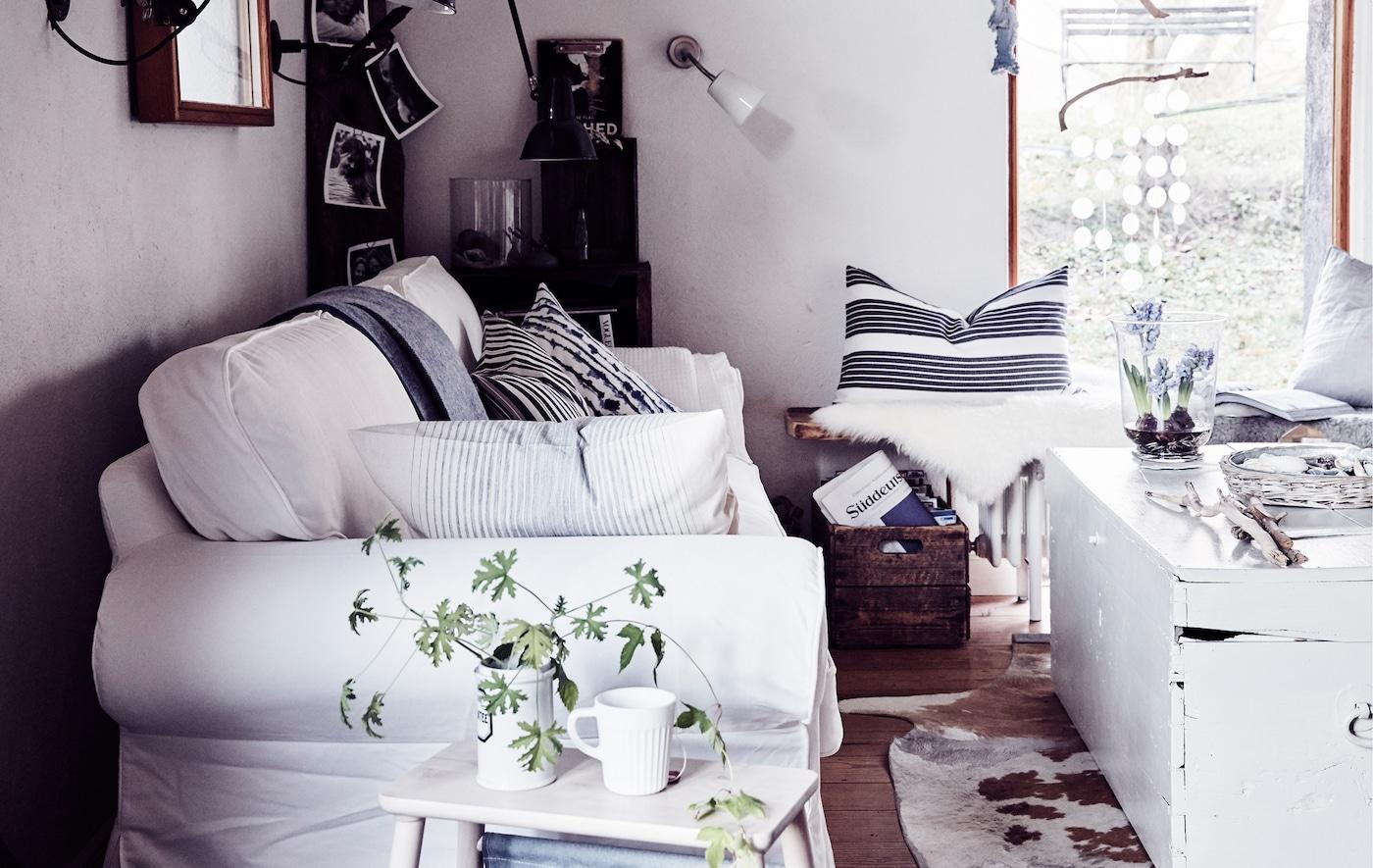 Um sofá branco de estilo tradicional numa sala, com almofadas às riscas, um baú de madeira vintage e materiais naturais.
