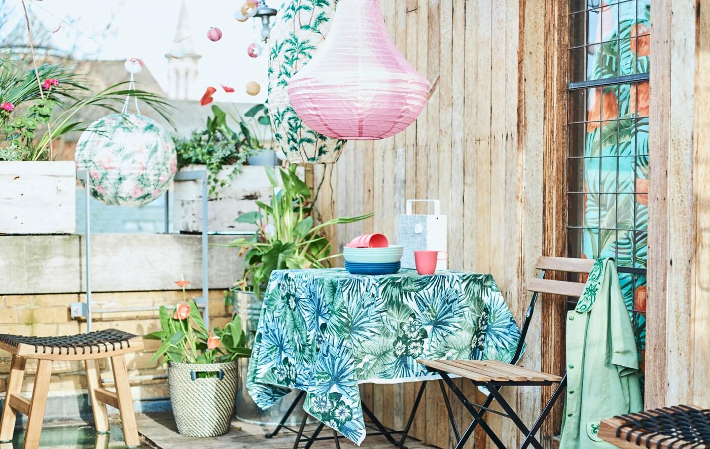 Um terraço urbano com uma mesa de exterior coberta com uma toalha com estampado de flores, cadeiras dobráveis, plantas em vasos e lanternas coloridas.