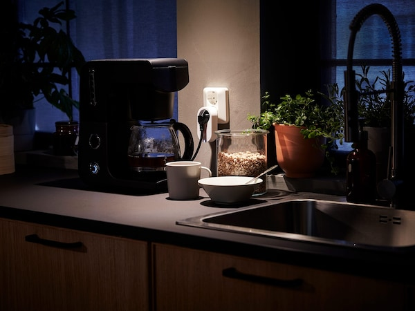 Uma bancada de cozinha com uma cafeteira ligada a uma tomada com controlador, e uma chávena e uma tigela ao lado de um lava-loiça.