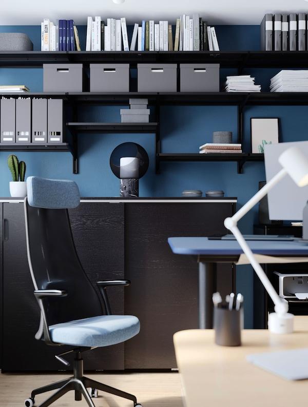 Uma cadeira JÄRVFJÄLLET ao lado de uma secretária com um candeeiro de secretária NYMÅNE em cima. Prateleiras ALGOT com arquivadores, caixas e livros ao fundo.