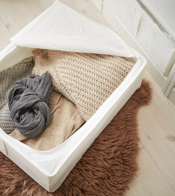 Uma caixa de arrumação SKUBB em branco com têxteis em cores e fibras naturais, sobre um tapete felpudo castanho.
