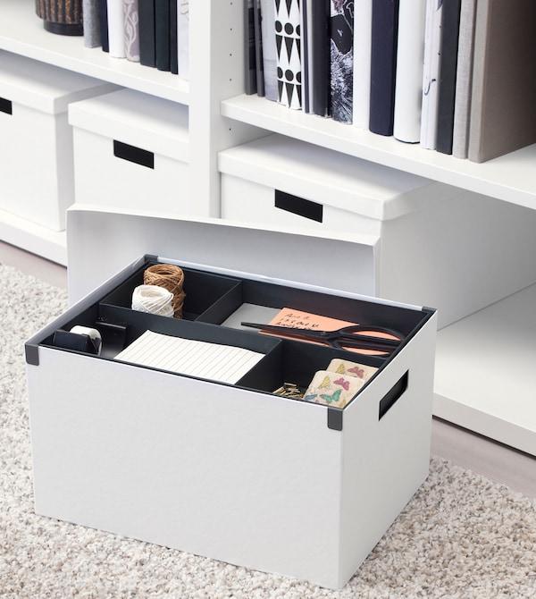 Uma caixa de arrumação TJENA em branco com material de escritório, sobre um tapete cinzento claro, com mais caixas em segundo plano.