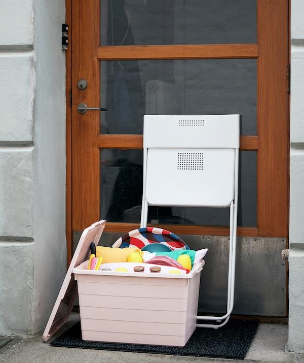 Uma caixa SOCKERBIT rosa repleta de acessórios para um piquenique e para brincar na porta de entrada de um edifício. Uma cadeira FEJAN dobrada encostada à porta.