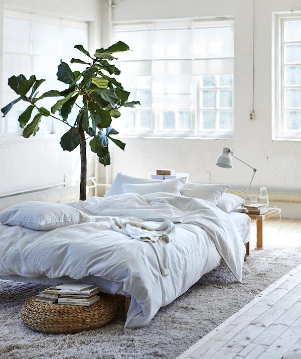 Uma cama baixa com roupa de cama branca em cima de um tapete em bege no centro de uma divisão branca.