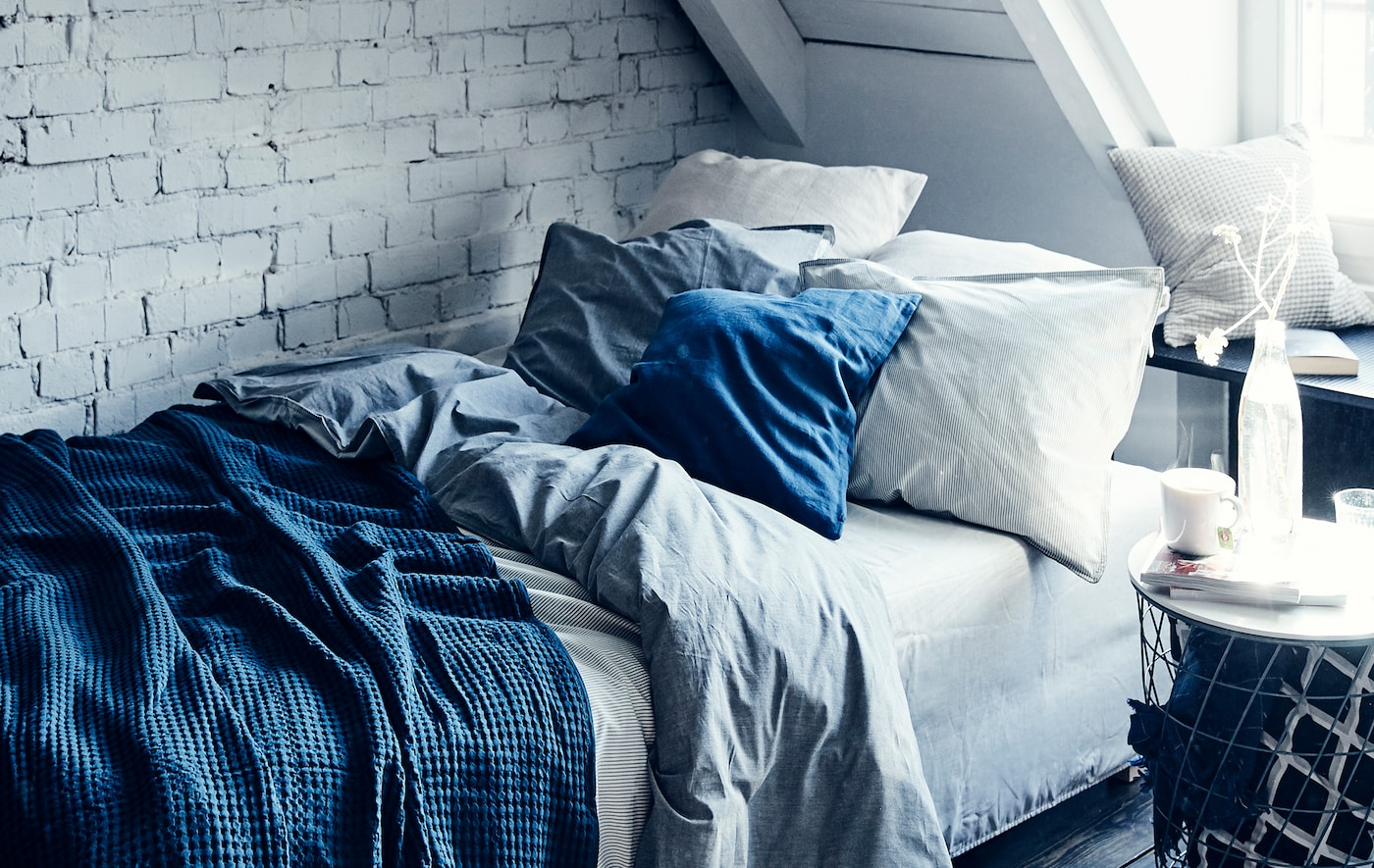 Uma cama com camadas de roupa de cama em azul e branco contra uma parede em alvenaria pintada de branco.