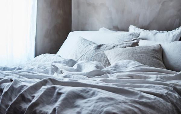 Uma cama com camadas de roupa de cama em cinzento e branco.