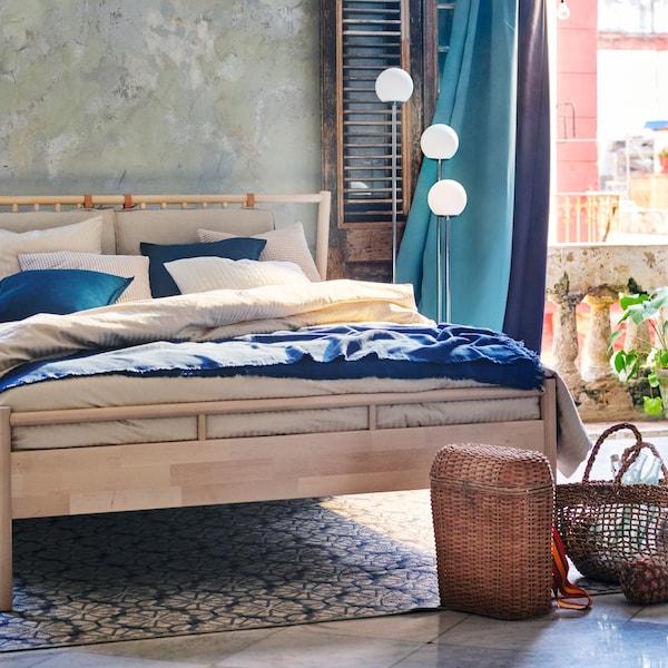 Uma cama em bétula com roupa de cama em bege e azul, com cortinados opacos em turquesa e roxo, e cestos de palha.
