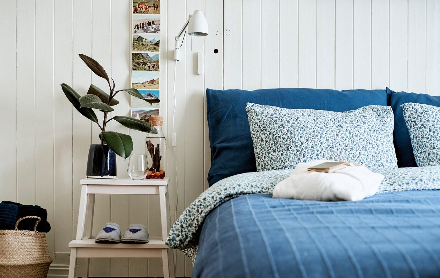 Uma cama feita com roupa de cama em azul, um banco que serve como mesa de apoio, sobre o qual se encontra uma garrafa de mesa com uma infusão e copos.