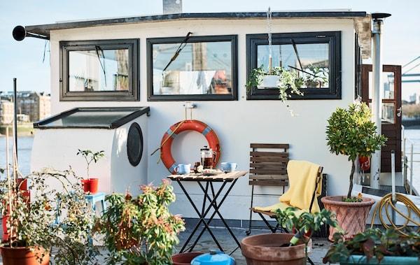 Uma casa-barco com plantas de exterior e uma cadeira no convés.