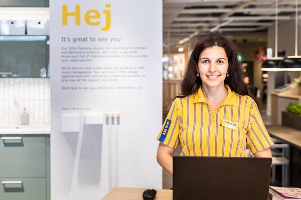 Uma colaboradora IKEA, com uma t-shirt amarela vestida, está atrás de um ponto de informação com um computador portátil, pronta para ajudar os clientes.
