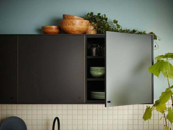 Uma cozinha com frentes de cozinha KUNGSBACKA, em preto, feitas a partir de madeira e garrafas de plástico PET recicladas.