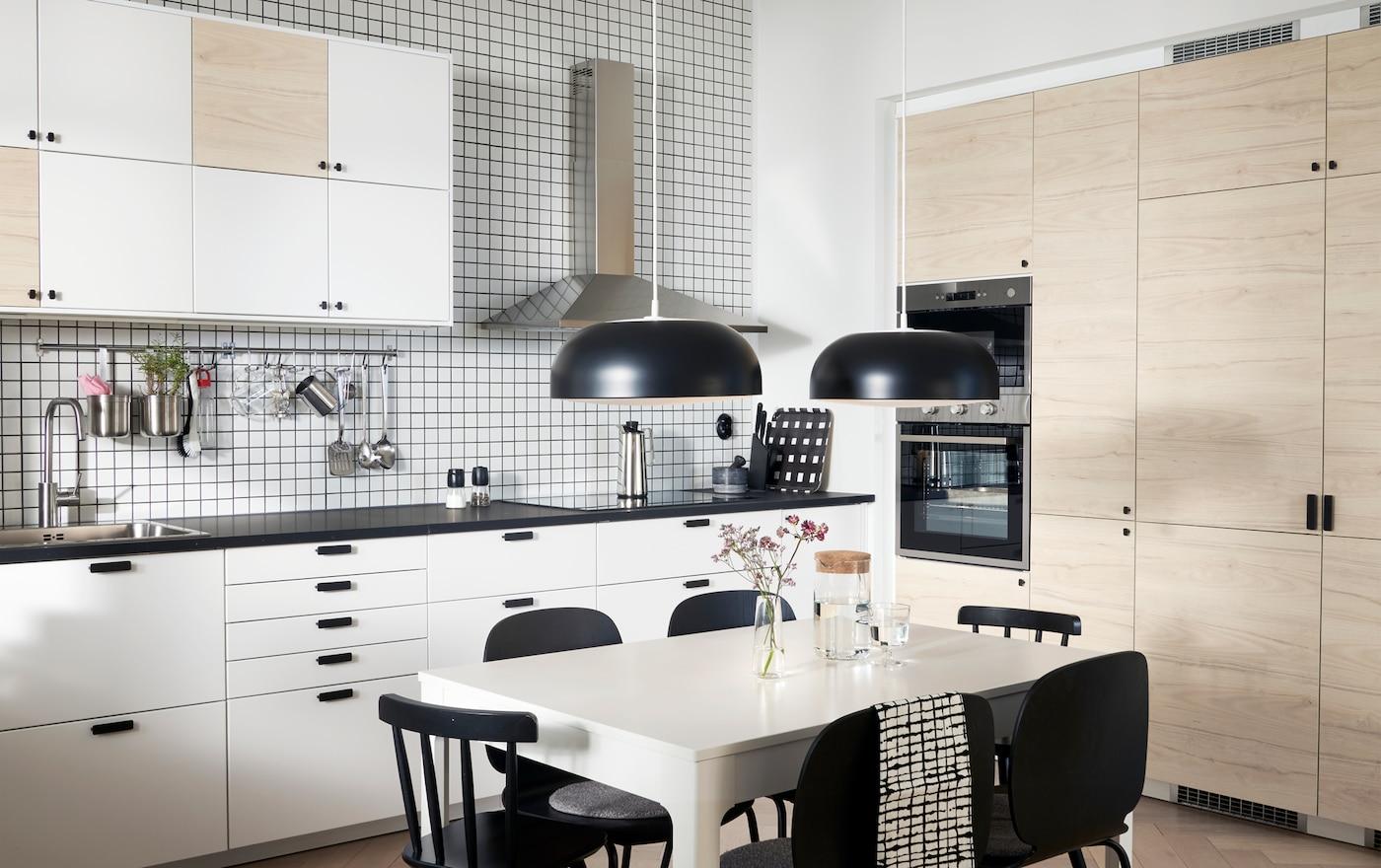 Uma cozinha com portas em branco e efeito freixo claro, dois candeeiros suspensos em preto, uma mesa em branco e cadeiras em preto.