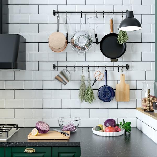 Uma cozinha com uma parede com azulejos brancos onde estão instaladas calhas em preto com ganchos com ervas aromáticas e utensílios de cozinha pendurados.