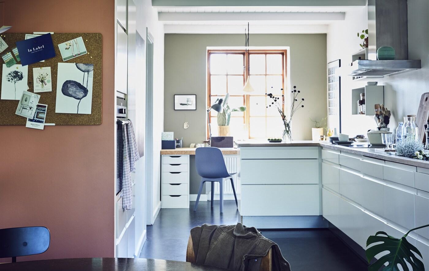 Uma cozinha e espaço de refeição em branco e em plano aberto.