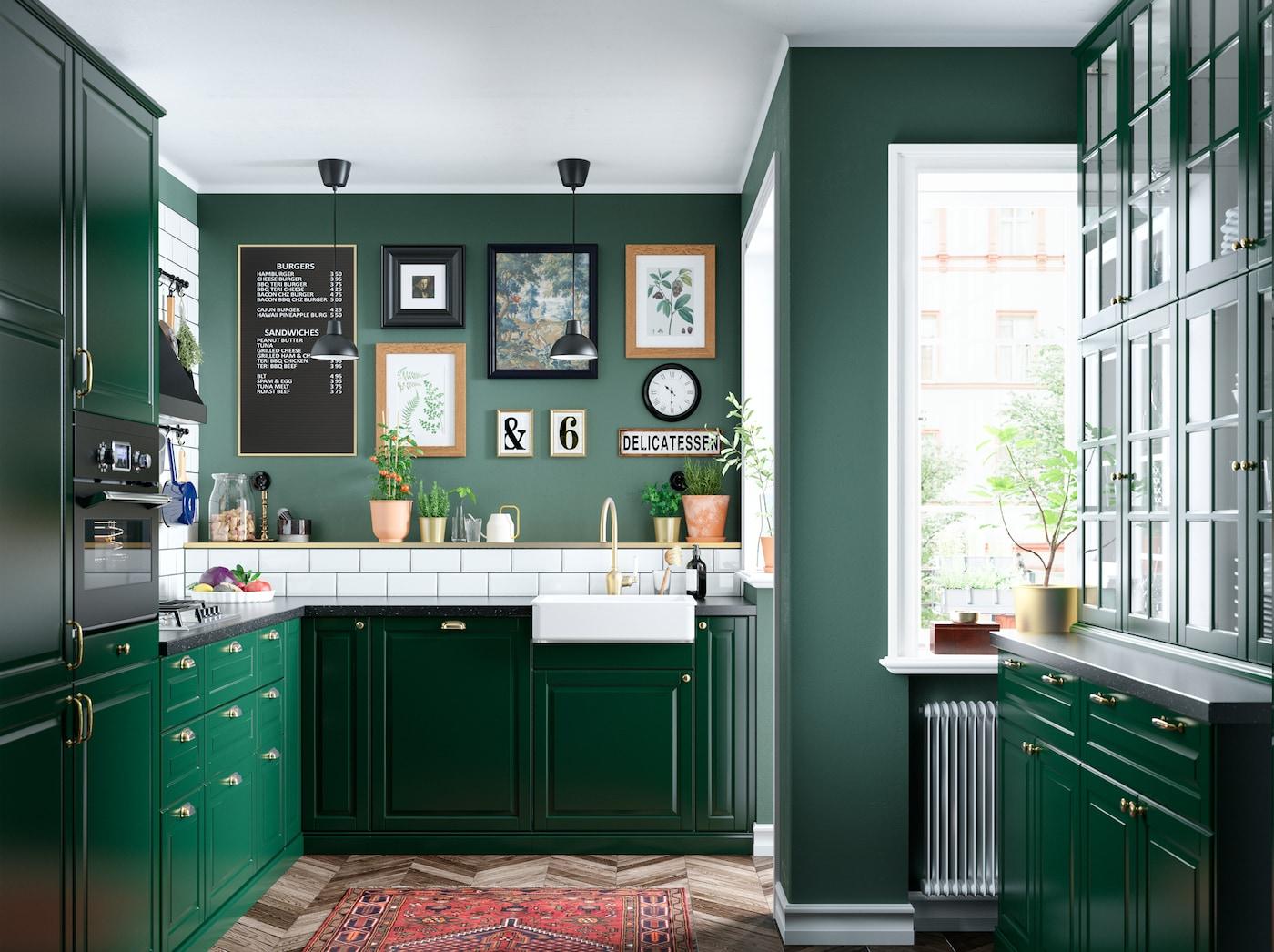 Uma cozinha em verde escuro com azulejos brancos, portas de vidro, torneira misturadora em cor de bronze e uma parede de fotografias com diversas molduras.