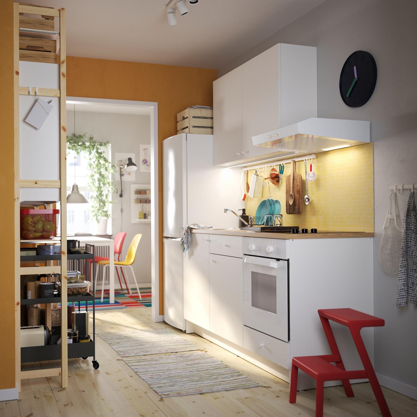 Uma cozinha KNOXHULT em branco, um escadote vermelho com dois degraus, uma estante em pinho, carrinhos pretos e cadeiras de cozinha coloridas.