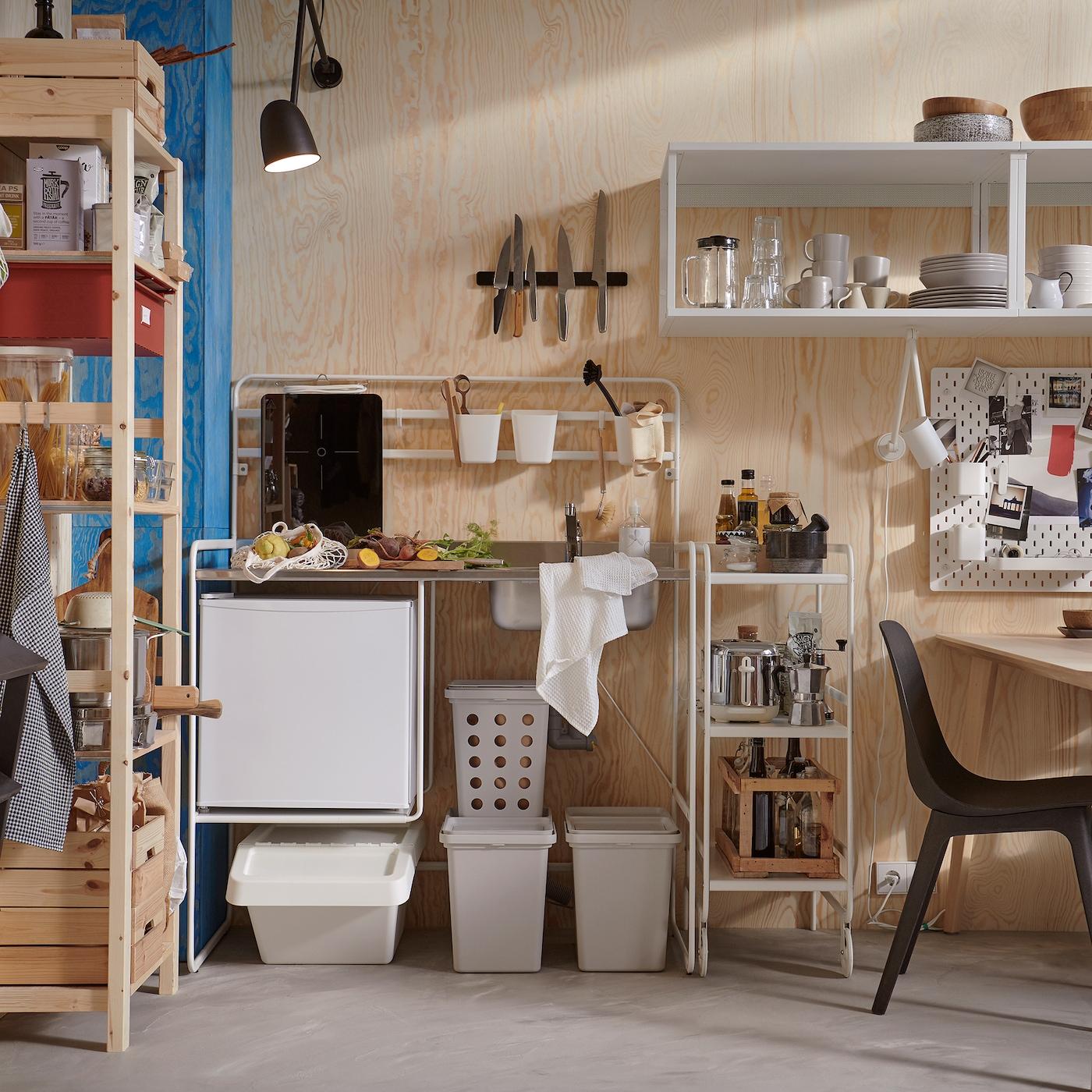 Uma cozinha pequena e luminosa com uma cozinha independente SUNNERSTA, caixotes para reciclagem em cinzento, um sistema de arrumação em pinho e cadeiras em preto.