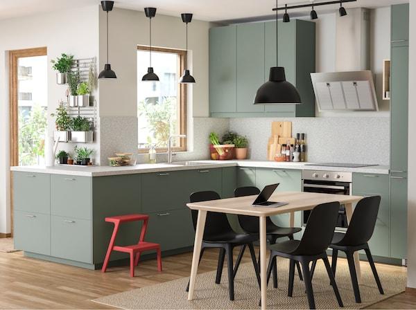 Uma cozinha verde acinzentada, uma mesa de refeição em madeira, cadeiras pretas, um candeeiro suspenso preto e muitas ervas aromáticas penduradas em calhas.