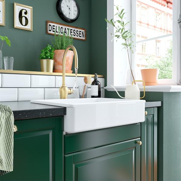 Uma cozinha verde com azulejos brancos, uma torneira misturadora em cor de bronze, um lava-loiça em cerâmica branca e um regador em tons de marfim e dourado.