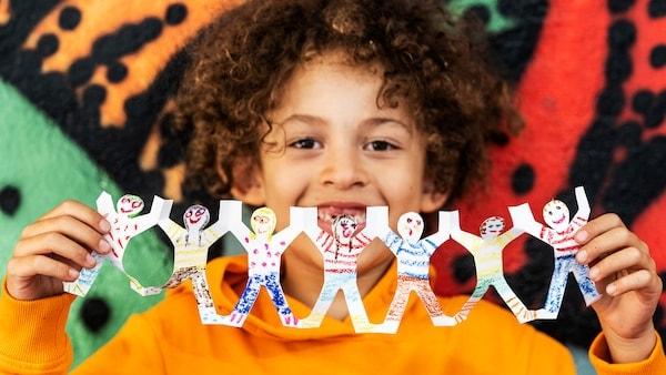 Uma criança com uma camisola laranja está a pegar numa grinalda colorida e alegre que representa crianças de mãos dadas.
