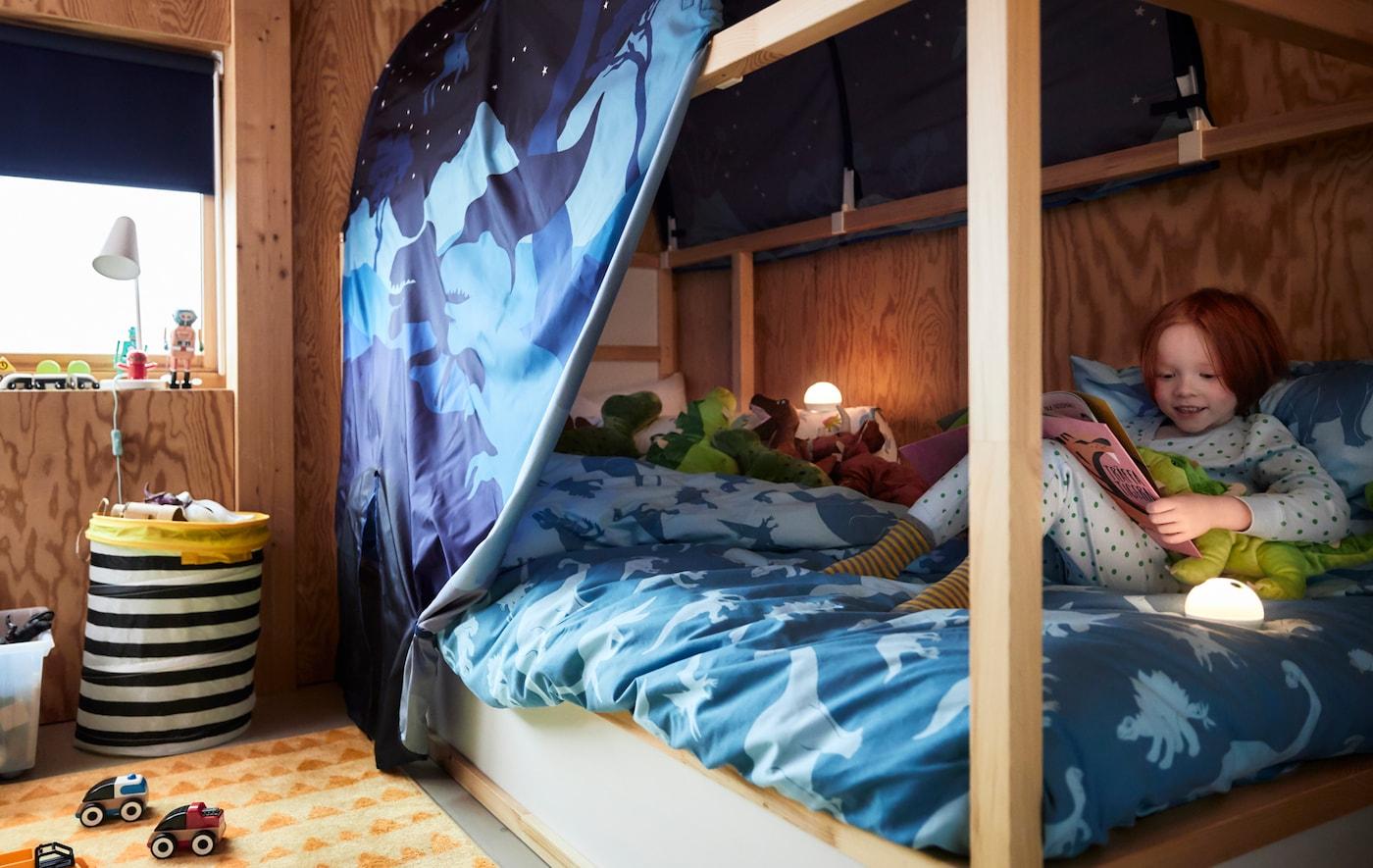 Uma criança está aninhada com o seu dinossauro de peluche numa cama KURA, a ler um livro de histórias debaixo de um dossel também ele com padrão de dinossauros.