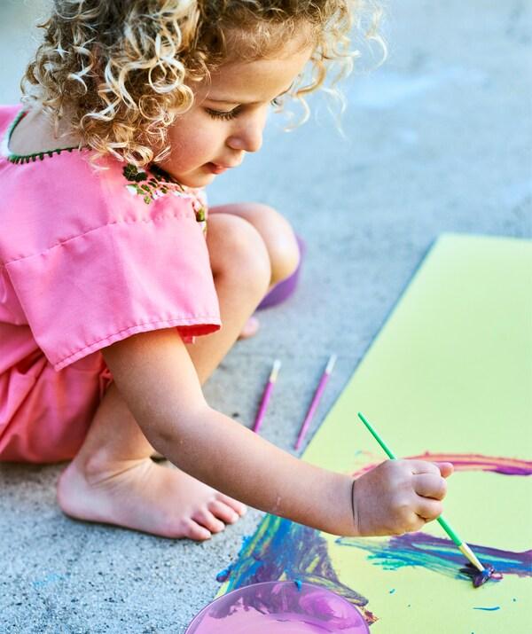 Uma criança pequena a pintar com cores brilhantes em papel amarelo, num chão de cimento.