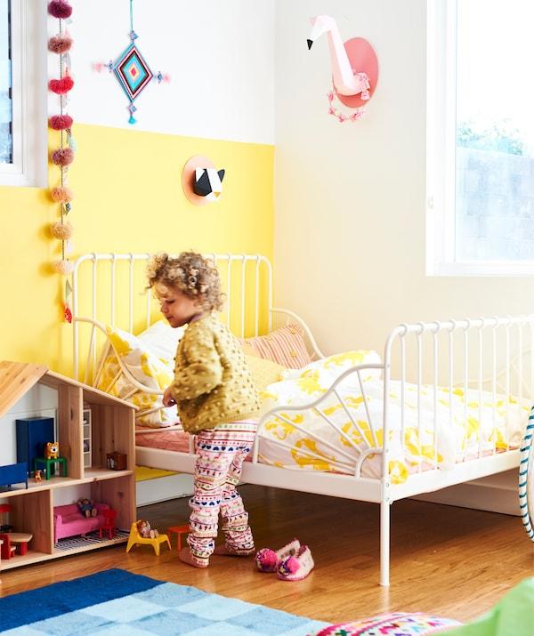 Uma criança pequena num quarto com uma parede amarela, uma cama com estrutura em branco, com roupa de cama em branco e amarelo, e uma casa de bonecas em madeira.