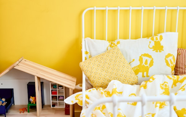 Uma estrutura de cama em branco, com roupa de cama em branco e amarelo e padrão de leões, encostada a uma parede amarela, ao lado de uma casa de bonecas em madeira.