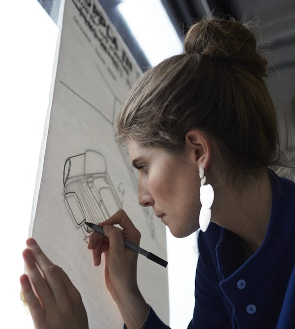 Uma estudante a desenhar esboços para o sofá DELAKTIG numa caixa de luz