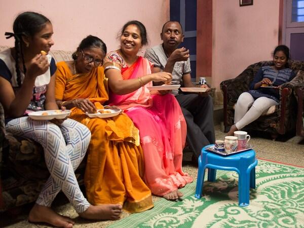 Uma família de cinco na Índia, sentada na sua sala, a comer juntos durante uma visita IKEA a casa.