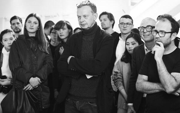 Uma fotografia a preto e branco do designer Tom Dixon e da sua equipa