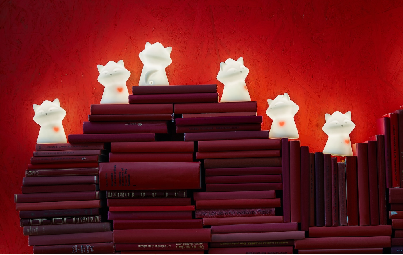 Uma luz de presença como o guaxinim LURIGA da IKEA afasta monstros e irradia segurança. Também tem um coração vermelho que pulsa, o que é uma forma doce de mostrar o seu amor por alguém. Pode empilhar vários livros vermelhos em forma de coração e colocar muitos LURIGA em cima.